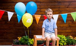 Portrait of young boy sitting on table at birthday party royalty free stock images