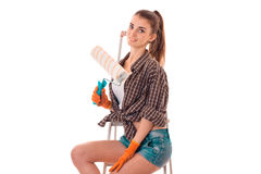 Portrait of young pretty brunette building woman with ladder and paint roller in hands makes renovation and looking at Royalty Free Stock Photography