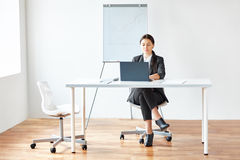 Portrait of young pretty business woman with laptop Stock Image