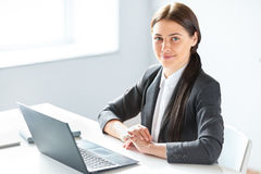 Portrait of young pretty business woman with laptop. In the office Royalty Free Stock Photos