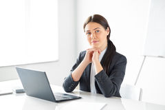 Portrait of young pretty business woman with laptop. In the office Royalty Free Stock Images