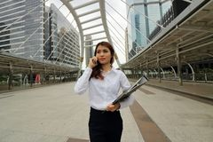 Portrait of young pretty business woman talking on phone at public outdoor background. stock photography
