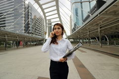 Portrait of young pretty business woman talking on phone at public outdoor background. Royalty Free Stock Photos