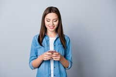 Portrait of young, pretty cute girl holding mobilephone in hands. Chatting with her lover while standing over grey background Royalty Free Stock Image