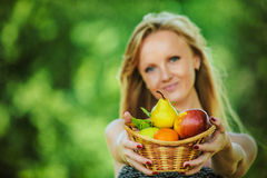 Portrait of young pretty fair-haired woman holding basket full o Stock Photo
