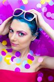 Portrait of young female in bathtub with pink water. Portrait of young pretty female girl adult woman fashion luxury model with blue hair relaxing wearing pink royalty free stock images
