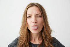 Portrait of young pretty funny girl looking at camera showing tongue over white background. Stock Photo
