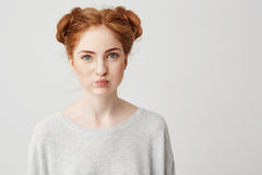 Portrait of young pretty ginger girl making funny face looking at camera over white background. Royalty Free Stock Photos