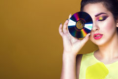 Portrait of young pretty girl with colourful artistic make-up and updo hair holding a CD in front of her eye royalty free stock images
