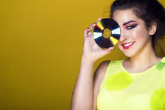 Portrait of young pretty girl with colourful artistic make-up and updo hair holding a CD in front of her eye and smiling Stock Photo