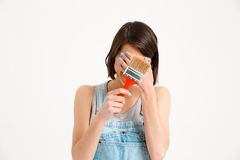 Portrait of young pretty girl, hiding face, holding painting b Royalty Free Stock Photo