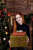 Portrait of a young girl holding a Christmas presents. Portrait of a young pretty girl holding a Christmas presents near a Christmas tree Stock Image