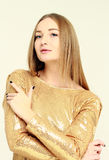 Portrait of a young pretty girl with long hair in a gold dress Stock Photo