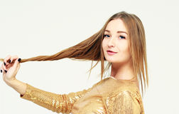 Portrait of a young pretty girl with long hair in a gold dress Royalty Free Stock Images
