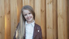 Portrait of the young, pretty girl smiles at camera at fence. 4K stock video footage