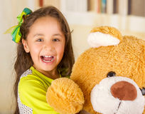 A portrait of a young pretty girl smiling and hugging her teddy bear over blurred background Stock Image
