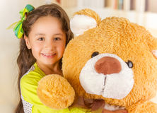 A portrait of a young pretty girl smiling and hugging her teddy bear over blurred background Stock Photography