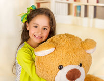 A portrait of a young pretty girl smiling and hugging her teddy bear over blurred background Stock Photos