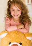 A portrait of a young pretty girl smiling and posing over her teddy bear head in a doctor office background Royalty Free Stock Photo