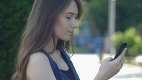 Portrait of young pretty girl using smartphone outdoor at street background. Portrait of a young pretty woman outdoor at street background stock video footage