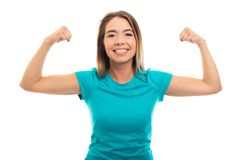 Portrait of young pretty girl wearing t-shirt flexing biceps gesture. Portrait of young pretty girl wearing t-shirt flexing biceps gesture isolated on white royalty free stock image