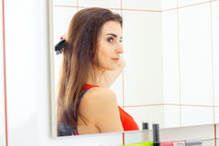 Portrait of a young pretty girl who looks in the mirror and combing her hair. Closeup Stock Photo