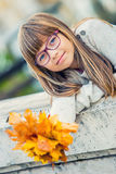 Portrait of a young pretty girl who was cheerfully playing with autumn maple leaves.Girl sitting on colorful autumn leaves. Autumn season royalty free stock image