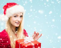 Portrait of young, pretty and happy teenage girl with a Christma. Beautiful, young and pretty girl in Christmas hat over background with snow Stock Photos
