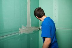 Hands plasterer at work. Application of the plaster on the wall. Portrait of young pretty man on construction site: male worker plastering walls with spatula Royalty Free Stock Photography