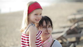Portrait of young pretty mother and little daughter on the beach stock footage