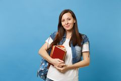 Portrait of young pretty pleasant woman student in denim clothes with backpack holding school books and ready to learn royalty free stock photo
