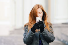 Portrait of young pretty redhead woman in blue dress and grey coat doing selfie photo at winter outdoors Stock Photo