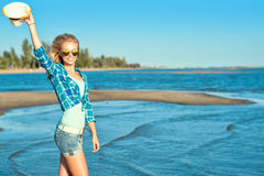 Portrait of young pretty smiling slim blond wearing mirrored heart shaped sunglasses walking along the seaside and waving a hat Royalty Free Stock Photos