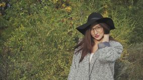 Portrait of young pretty smiling woman in black hat and glasses on autumn street. Portrait of young pretty smiling woman in black hat and glasses on the autumn stock video footage