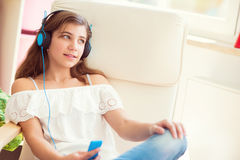 Portrait of young pretty teenage girl listening music with moder Stock Photography