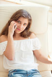 Portrait of young pretty teenage girl speaking with handy. In sunny room Stock Photo