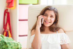 Portrait of young pretty teenage girl speaking with handy. In sunny room Stock Photos