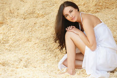 Portrait of young pretty woman. Portrait of young charming brunette woman wearing white dress sitting in sawdust Stock Images
