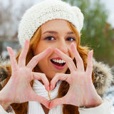 Portrait of young pretty woman. Portrait of beautiful young red hair woman outdoors in winter looking at camera and enjoying snow, Making heart shape of her arms royalty free stock images
