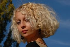 A portrait of a young pretty woman with a blond curly hair and blue eyes under the blue sky. A portrait of a young pretty woman with a blond curly hair and blue Royalty Free Stock Photo