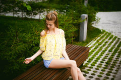 Young beautiful woman, warm summer sunny day. Portrait of a young pretty woman in blue denim jeans shorts sitting on a bench in courtyard of a residential royalty free stock photography