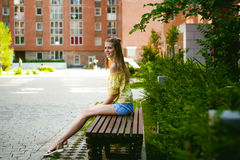Young beautiful woman, warm summer sunny day. Portrait of a young pretty woman in blue denim jeans shorts sitting on a bench in courtyard of a residential royalty free stock photo