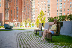 Young beautiful woman, warm summer sunny day. Portrait of a young pretty woman in blue denim jeans shorts sitting on a bench in courtyard of a residential stock photos
