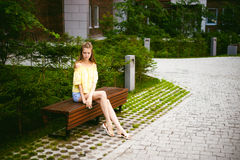 Young beautiful woman, warm summer sunny day. Portrait of a young pretty woman in blue denim jeans shorts sitting on a bench in courtyard of a residential royalty free stock image