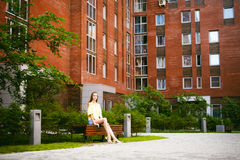 Young beautiful woman, warm summer sunny day. Portrait of a young pretty woman in blue denim jeans shorts sitting on a bench in courtyard of a residential stock images