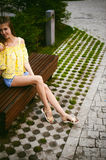 Young beautiful woman, warm summer sunny day. Portrait of a young pretty woman in blue denim jeans shorts sitting on a bench in courtyard of a residential stock photo
