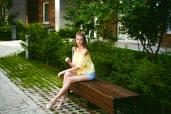 Young beautiful woman, warm summer sunny day. Portrait of a young pretty woman in blue denim jeans shorts sitting on a bench in courtyard of a residential stock photography