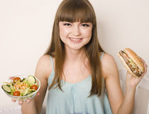 Portrait of young pretty woman with burger and salad, making choice Royalty Free Stock Photography
