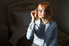 Portrait of young pretty woman in dramatic light at the hotel room. Successful woman royalty free stock image