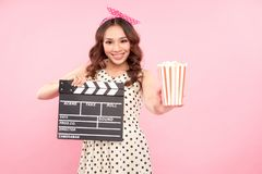 Portrait of young pretty woman in glasses with clapperboard. Film production and movie making concept royalty free stock photography